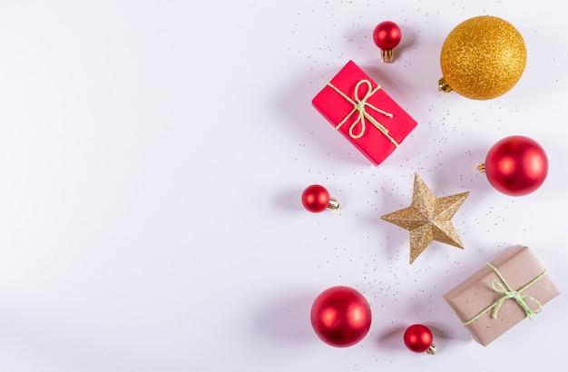 Composizione di natale. decorazioni rosse e dorate dei regali di natale, su bianco. vista dall'alto, copyspace.