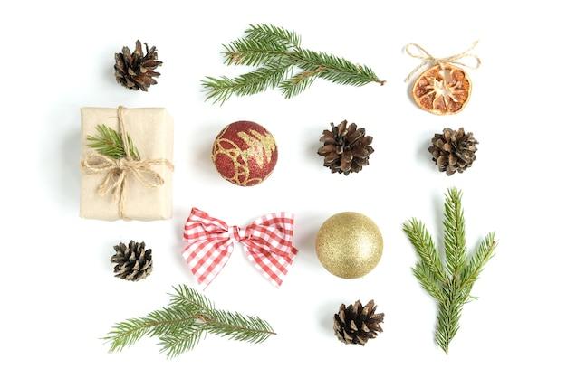 Composizione di natale di palle di natale, confezione regalo, coni e rami di abete isolati su superficie bianca. appartamento laico, vista dall'alto, copia dello spazio