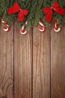 Composizione di natale di rami di alberi, caramelle e decorazioni su fondo di legno. vista dall'alto. copia spazio.