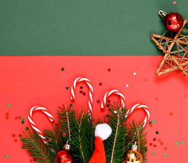 Composizione di natale di rami di un albero, cappello di babbo natale, caramelle stelle, su rosso e verde