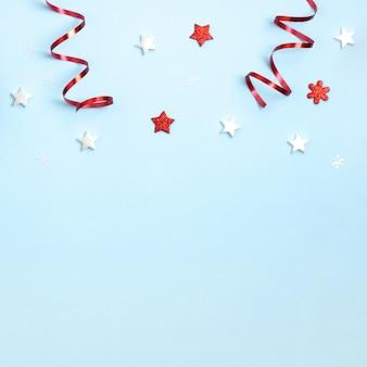 Composizione di natale e capodanno. frame frome giocattoli di natale rosso e bianco su carta blu. vista dall'alto, piatto, copyspace