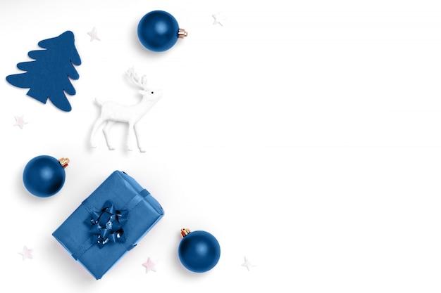 Composizione di natale e capodanno. telaio da palle rosse, stelle bianche, albero di natale, cervi su carta bianca sullo sfondo. vista dall'alto, disteso, copia spazio. colore alla moda dell'anno 2020.
