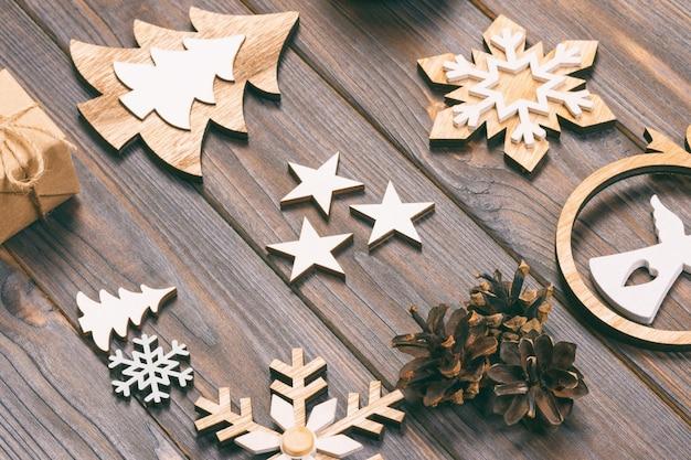Composizione di natale. fiocchi di neve di natale, albero di natale e angelo in una cornice su un legno.