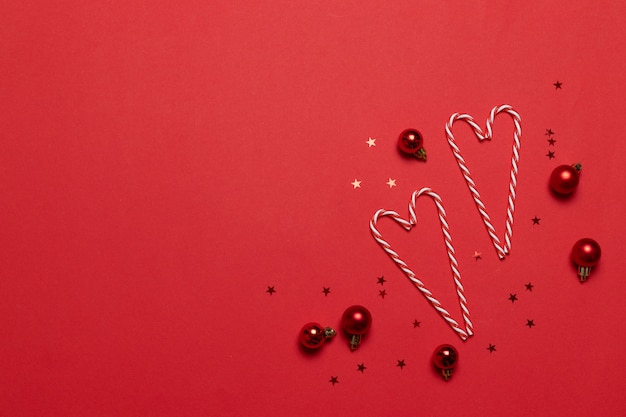 Composizione di natale. le canne di caramella nell'amore modellano su priorità bassa rossa. natale, inverno, concetto di nuovo anno. vista piana, vista dall'alto, copia spazio