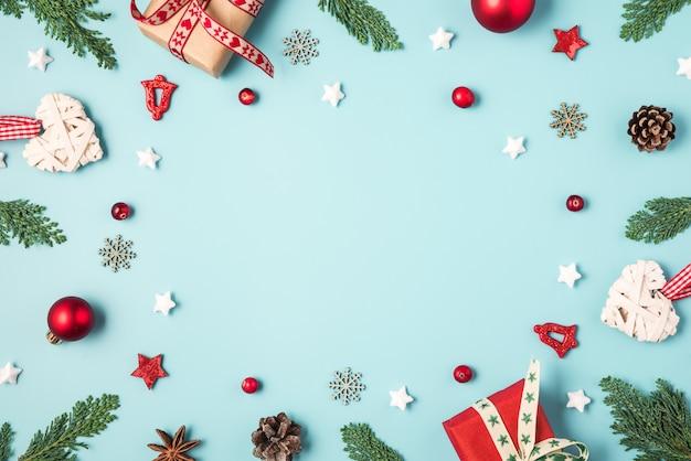 Composizione di natale o felice anno nuovo. cornice fatta di rami di abete, scatole regalo, pigne e decorazioni natalizie rosse
