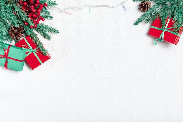 Composizione di natale. regali di natale, rami di pino, luce natalizia, ghirlanda su sfondo bianco. vista dall'alto.