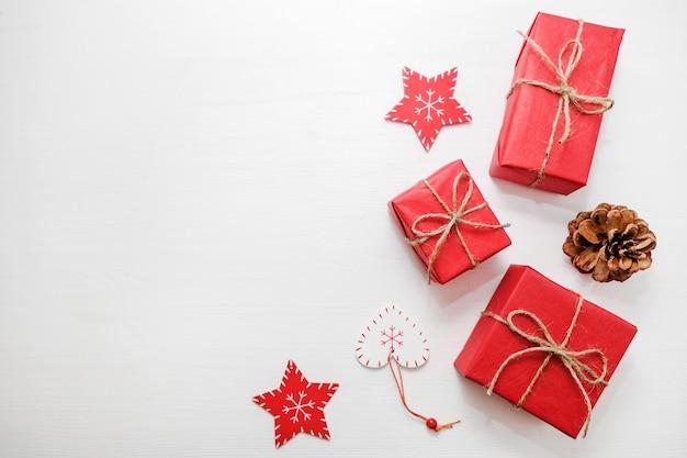 Composizione di natale regali, pigne, decorazioni rosse su sfondo bianco.