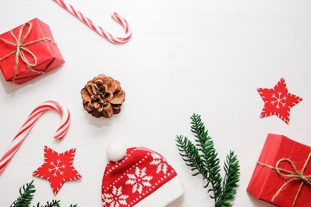 Composizione di natale regali, rami di abete, decorazioni rosse su sfondo bianco.