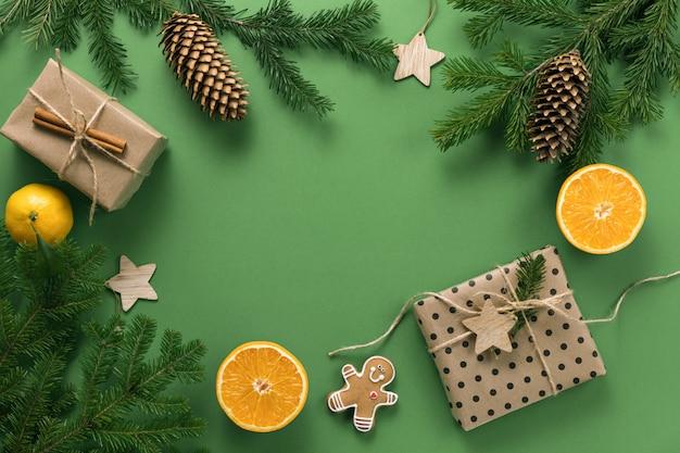 Composizione di natale. regali, rami di abete rosso, pigna e arance, su uno sfondo verde. natale, inverno, concetto di nuovo anno. lettino piatto, vista dall'alto, spazio di copia