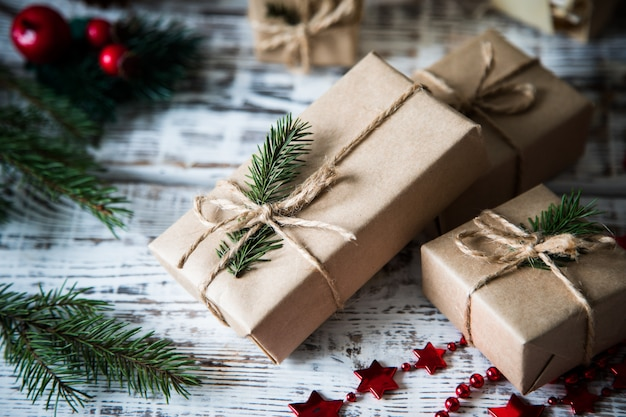 Composizione di natale regalo di natale, pigne, rami di abete su fondo di legno bianco.