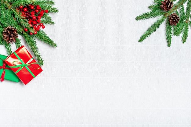 Composizione di natale. regalo di natale, pigne, rami di abete su sfondo bianco carta ondulata. appartamento laico, vista dall'alto, copia dello spazio.