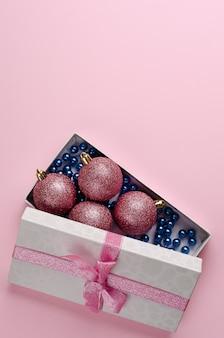 Composizione di natale. scatola regalo aperto con palline e ghirlanda blu su rosa pastello. verticale verticale. copyspace