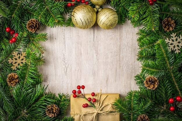Composizione di natale su fondo di legno per i saluti delle vacanze invernali. regali di natale, pigne, vischio, fiocchi di neve su uno sfondo scuro con texture.