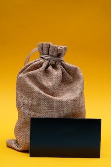 Composizione di natale su un giallo. borsa regalo in tela di babbo natale.