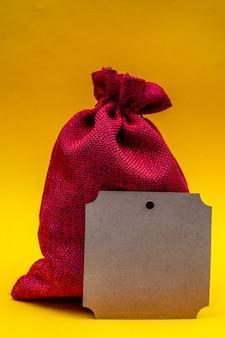 Composizione di natale su un giallo. sacchetto regalo in tela rossa di babbo natale.