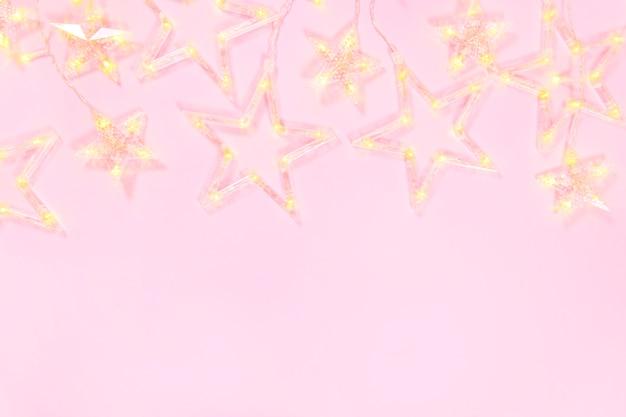 Composizione di natale su uno sfondo rosa. cornice di ghirlanda di stelle. concetto di natale. vista piana, vista dall'alto e copia spazio