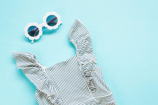 Composizione di occhiali da sole moderni bianchi e più elementi sul blu