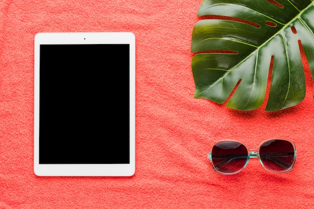 Composizione di occhiali da sole tablet e foglia di pianta