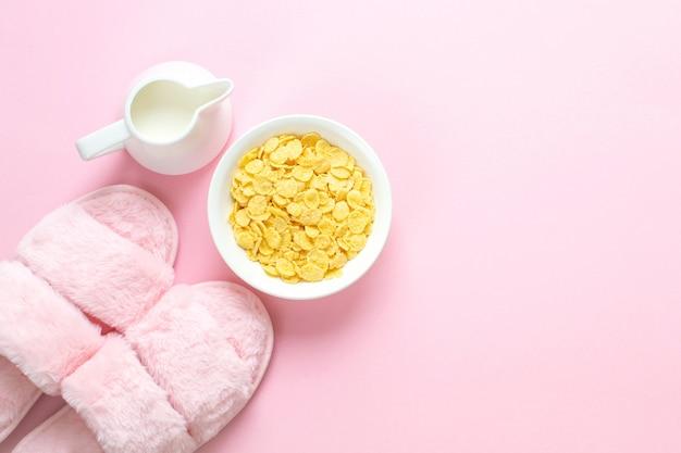 Composizione di pantofole in pelliccia sintetica e bevande su rosa chiaro