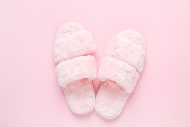 Composizione di pantofole in pelliccia sintetica su rosa chiaro