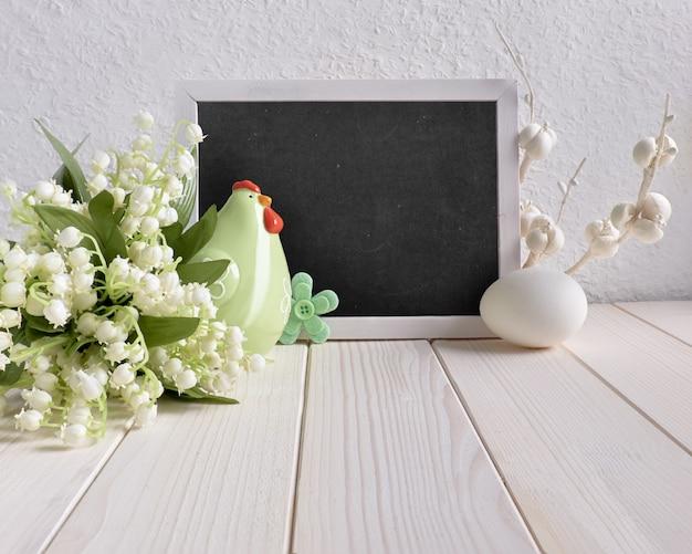 Composizione di pasqua con lavagna decorata con gallina in ceramica, uova e fiori di mughetto, testo