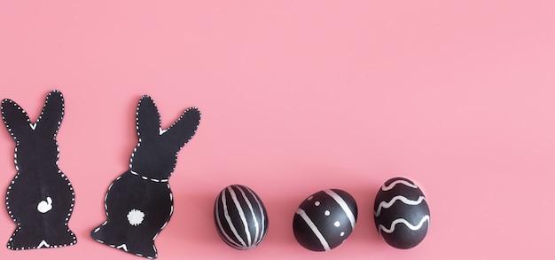 Composizione di pasqua con le uova e il coniglietto di pasqua su un tavolo rosa