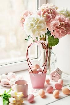 Composizione di pasqua con ortensie rosa e bianche in vaso, tulipani gialli e uova rosa