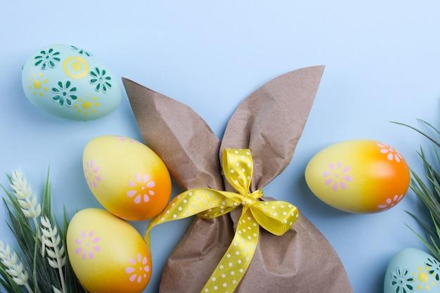 Composizione di pasqua con pacchetto di carta artigianale a forma di coniglietto, uova di pasqua colorate e fiori. vista piana, vista dall'alto,