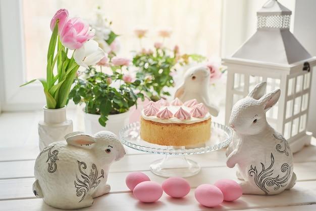 Composizione di pasqua con torta dolce con glassa di fragole, coniglietti in ceramica, uova rosa e rose