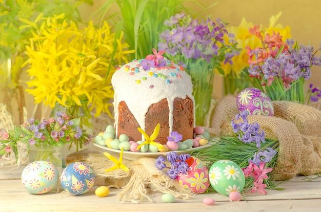 Composizione di pasqua con torta, uova colorate e fiori