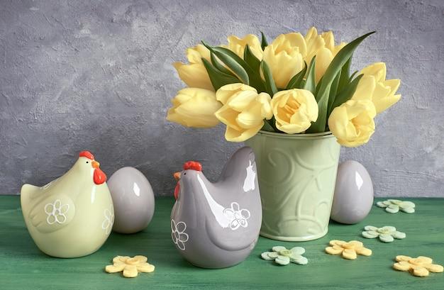Composizione di pasqua con tulipani gialli e galline in ceramica con uova di pasqua in verde, giallo e grigio