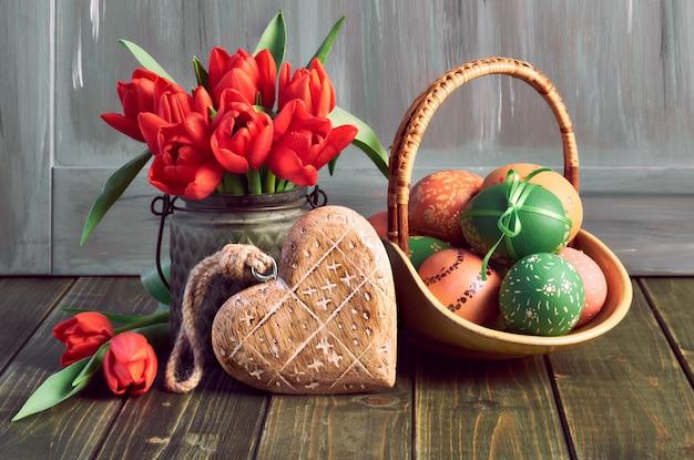 Composizione di pasqua con tulipani rossi, cuore in legno e un cesto di uova di pasqua colorate su legno