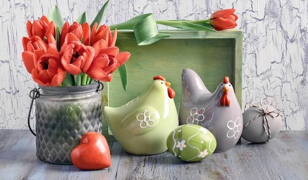 Composizione di pasqua con tulipani rossi, galline in ceramica e uova di pasqua su legno chiaro