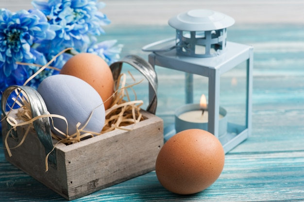 Composizione di pasqua con uova, fiori blu e lume di candela