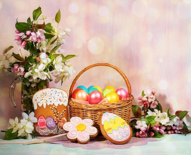 Composizione di pasqua di cesto di uova di pasqua dipinte, pan di zenzero dipinto, ramoscelli di melo