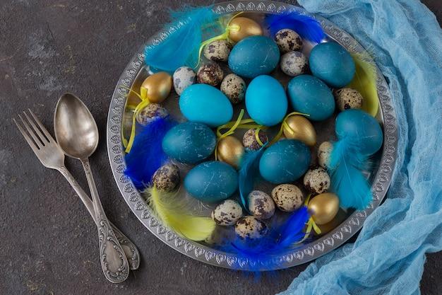 Composizione di pasqua: in un piatto d'argento si trovano uova blu, uova d'oro, uova di quaglia e piume e posate