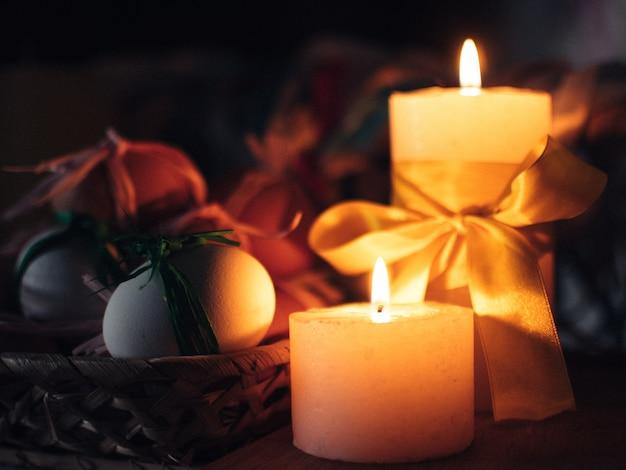 Composizione di pasqua le candele bruciano nel buio