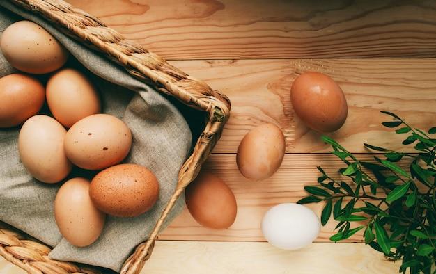 Composizione di pasqua le uova di pasqua si trovano in una scatola di uova accanto a rami verdi su uno sfondo di legno chiaro foto di concetto di pasqua dall'alto