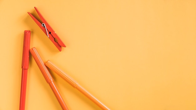 Composizione di pennarelli colorati e pin rosso