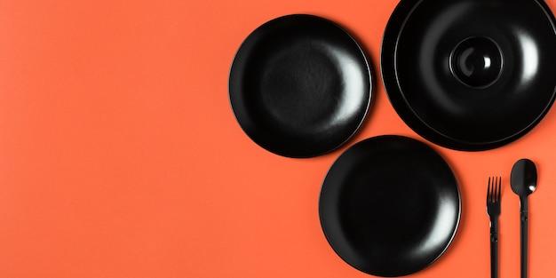 Composizione di piatti di diverse dimensioni su sfondo arancione con copia spazio