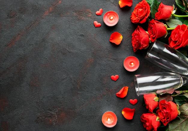 Composizione di san valentino con fiori, candele e bicchieri di champagne