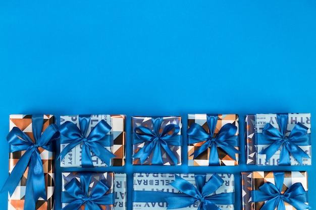 Composizione di scatole regalo su sfondo blu. spazio per testo piatto.