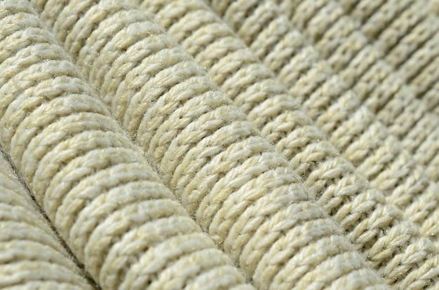 Composizione di un maglione lavorato a maglia giallo morbido. macro trama di legature in filati
