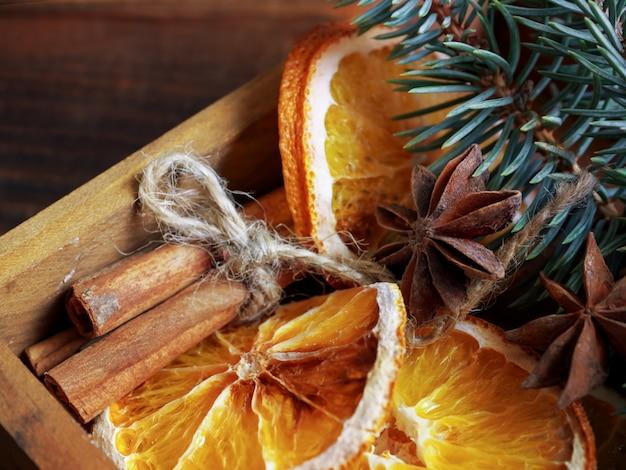 Composizione di vacanze di natale con rami e arance secche con bastoncini di cannella