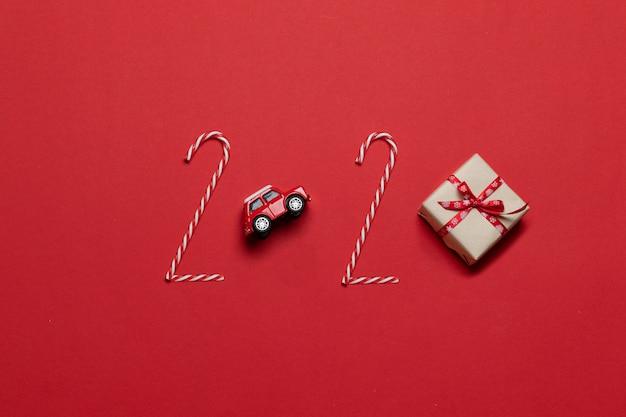 Composizione di vacanze di natale e capodanno 2020 scritte di varie decorazioni auto giocattolo rosso, confezione regalo