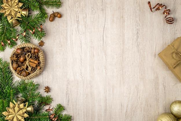 Composizione di vacanze di natale per i tuoi messaggi di vacanze invernali. regalo di natale, cestino tradizionale, stelle di anice, pigne, bastoncini di cannella, campane d'oro, fiocchi di neve e palle di natale su legno