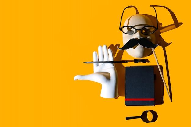Composizione di vari oggetti, occhiali, lente d'ingrandimento, matita, baffi, farfalla, mano, quaderno, maschera.