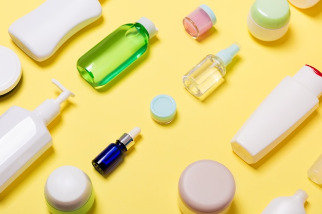 Composizione di vasetti e bottiglie cosmetici di dimensioni diverse su sfondo giallo