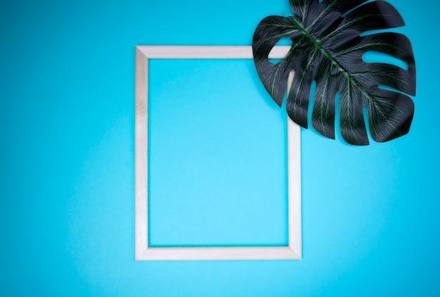 Composizione estiva con foglie di monstera e cornice foglie tropicali, cornice vuota su sfondo blu pastello.