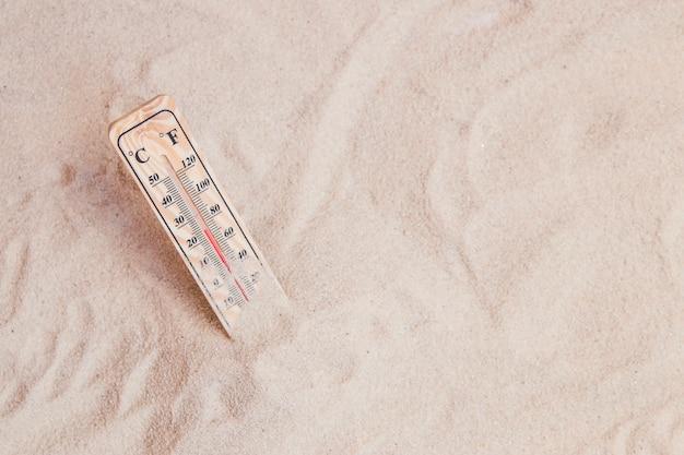 Composizione estiva con sabbia e termometro